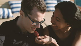 Two young people laugh and eat strawberries outdoors. Close-up view on faces of happy couple. Attractive dark-haired man in black T-shirt and glasses, tells stock video footage