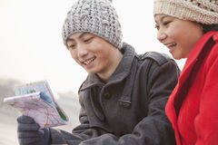 Two young people looking at map outside in winter, Beijing Stock Image