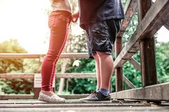 Cute teen couple standing together on a wooden bridge. Stock Photos