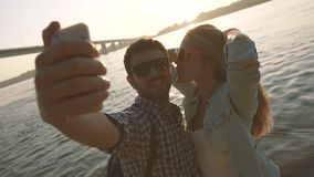 Two young people in love having fun on the river bank and taking pictures of themselves stock video