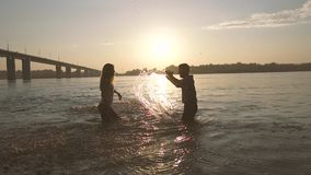 Two young people in love having fun with water. They jump in water and splash stock video footage