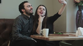 Two young people makeing selfy while in cafe. Two young peoplemakeing selfy while sitting at a table in cafe with window, smiling, making gestures stock video footage