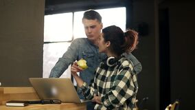 Two young people, young man and a girl, typing something, using laptop. Spending time together. Open co-working space. Indoors area stock footage