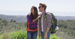Two young people in mountains. Young female and man smiling and looking away while hiking in mountains with picturesque view of background stock video