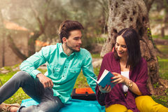 Two young people on picnic sitting on blanket. Under the olive trees Royalty Free Stock Photo