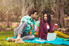 Two young people on picnic sitting on blanket. Under the olive trees Stock Image