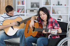 Two young people playing guitars one in wheelchair Stock Images