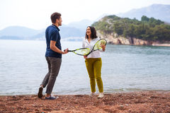 Two young people playing on the seashore speedminton - badminton Royalty Free Stock Photos
