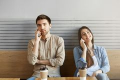 Two young people in a quarrel sitting near each other in cafeteria, looking aside, drinking coffee and talking on phones.  Royalty Free Stock Photos