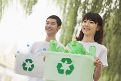 Two Young People Recycling Plastic Bottles Royalty Free Stock Photos