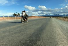 Two young people riding a motorcycle on a completely empty road royalty free stock photo