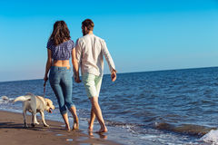 Two young people running on the beach kissing and holding tight with dog Stock Photography