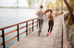 Two young people are running on the bridge near river. They are doing this exercise together. There is a bridge that. Goes across the river Stock Photo