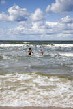 Two young people running to the blue sea Royalty Free Stock Photography