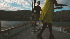 Two young people sailing on sailboat and dancing on deck outdoors. Beautiful woman, dark-skinned metis, in yellow short dress, actively dances, quickly moving stock video