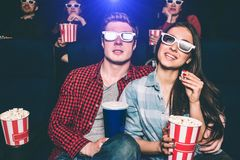 Two young people are sitting close to each other. They have special glasses on their faces to watch movie. Girl is. Holding basket with popcorn and one piece of Stock Photos