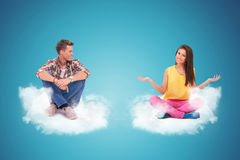 Two young people sitting on clouds welcoming Stock Photo