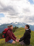 Two young people sitting on the grass and holding hands Royalty Free Stock Image