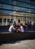 Two young people sitting in the sun on square in Barcelona chatting royalty free stock image