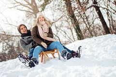 Two young people sliding on a sled royalty free stock images