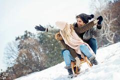 Two young people sliding on a sled stock images