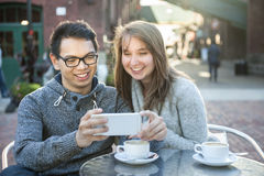 Two young people with smartphone in cafe Royalty Free Stock Photos