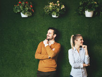 Two young people standing over a grass wall Royalty Free Stock Images