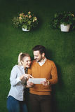 Two young people standing over a grass wall, holding a tablet Royalty Free Stock Photos