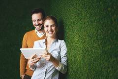 Two young people standing over a grass wall, holding a tablet Stock Photos