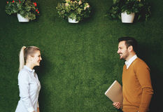 Two young people standing over a grass wall, holding a tablet Royalty Free Stock Image