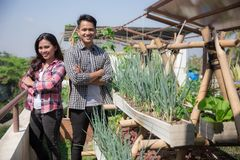 Young people with urban farming concept. Two young people standing proudly in front of their garden. urban farming concept Royalty Free Stock Images