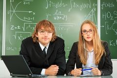 Teachers. Two young people in suits studying at a classroom Royalty Free Stock Image