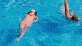 Two young people swimming in the pool stock video footage