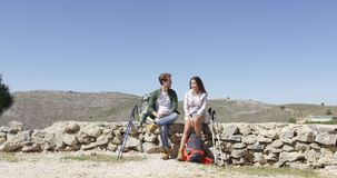 Two young people taking rest. Young loving couple sitting on rock fence while hiking in mountains in summer time stock video