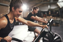 Two young people training on cycling machines stock photography
