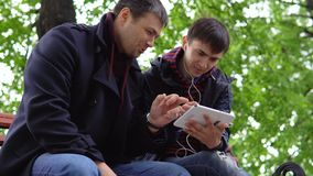 Two young people use a tablet in the park. Two young people sit in a city park on a bench, look at the tablet, smile and talk stock footage