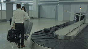 Two young people wait their baggage near the baggage claim desk in airport. The action takes place at the arriving hall of the airport near the baggage claim stock video footage