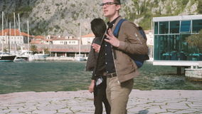 Two young people walk down beach, looking at nature. Attractive caucasian man, wearing glasses, with backpack, brown trousers and windbreaker, walking along stock video