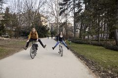 Two young people, 20-29 years old, riding a bicycle in a park with legs stretched, silly, laughing and having fun.  stock image