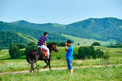 Two young person and horse on the summer meadow. The photo was taken in huamugou national forest park Hexigten banner Chifeng city Nei Monggol Autonomous Region Stock Photos