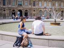 Two young person man and woman rest and sunbathe near the fountain on the square in front of the Louvre in Paris stock photography