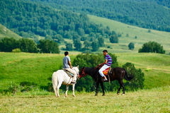 Two young person and two horses on the summer meadow. The photo was taken in huamugou national forest park Hexigten banner Chifeng city Nei Monggol Autonomous Stock Photos