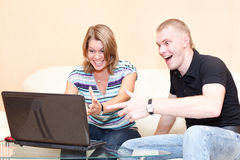 Two young persons playing in games on laptop. Royalty Free Stock Photo