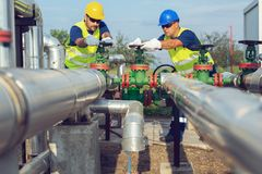 Two petrochemical workers inspecting pressure valves on a fuel tank. Two young petrochemical workers inspecting pressure valves on a fuel tank royalty free stock photos