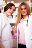 Two young pharmacist woman behind the desk Stock Photos