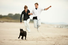 Two young poeple jumping on the beach  and holding Royalty Free Stock Images