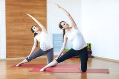 Two young pregnant fitness model in sportswear doing yoga, pilates training, lunge exercise, Utthita Parsvakonasana, Extended Side stock photography