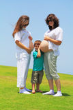 Two young pregnant women and a small son Stock Images