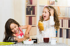 Two young preschooler girls eating at the table Royalty Free Stock Images