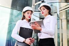 Two young pretty business women industrial engineers in construction helmets with a tablet in hands on a glass building Royalty Free Stock Photos
